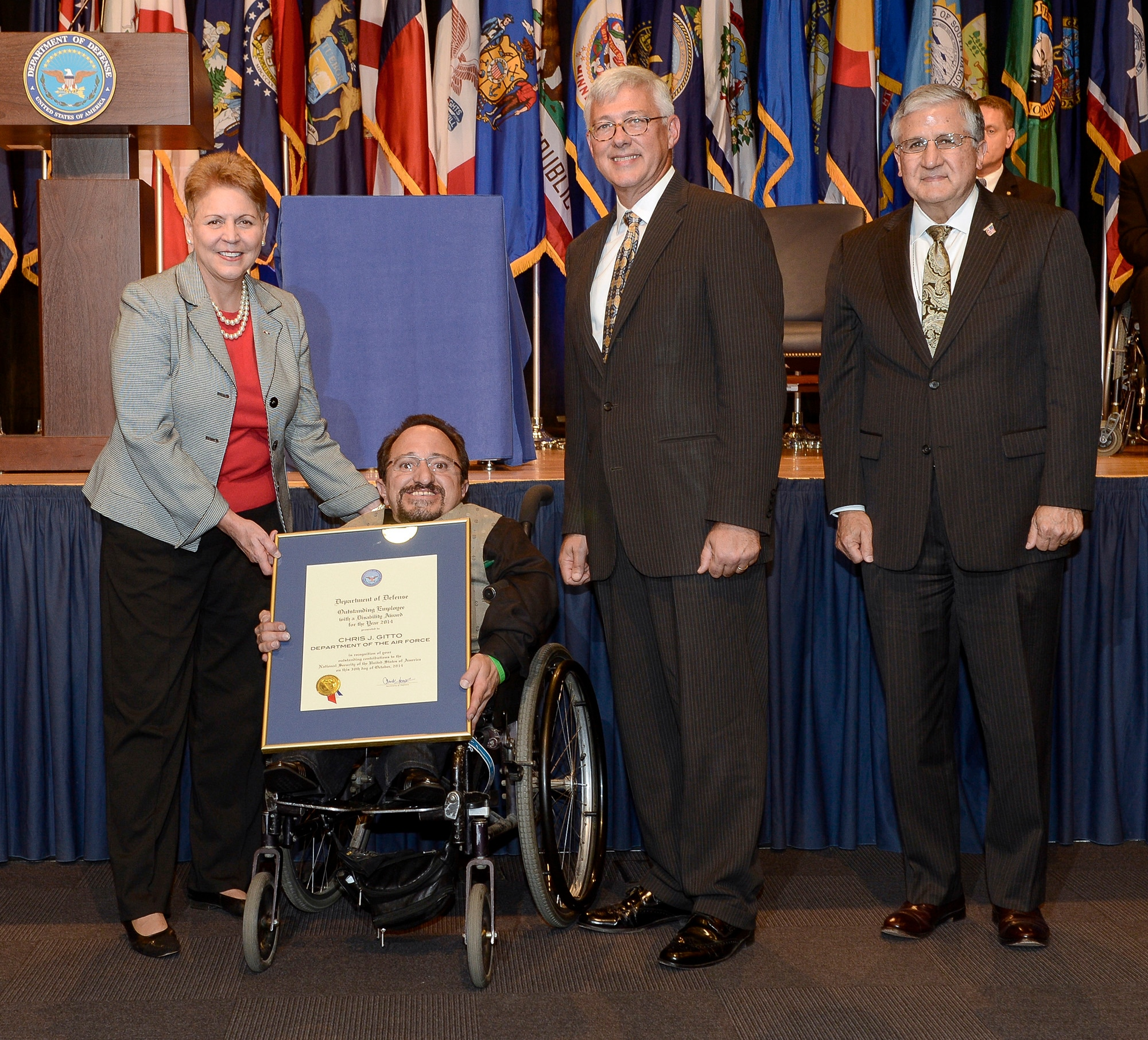 Under Secretary for Defense Jessica Garfola, Principal Deputy Assistant Secretary for Manpower and Reserve Affairs Daniel Sitterly and Assistant Deputy Chief of Staff for Manpower, Personnel and Services Robert Corsi present Chris Gitto with the 2014 DOD Disability Award during a ceremony Oct. 30, 2014, at the Pentagon. The DOD Disability Awards ceremony honors service components for outstanding achievements in the hiring, retention and advancement of individuals with disabilities.  Gitto is a technical information specialist from Kirkland Air Force Base, N.M. (U.S. Air Force photo/Andy Morataya)