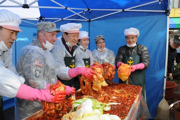 Far East District deputy commander Lt. Col. Julie D'Annunzio (2nd from right) and plans officer Cpt. Lex Oren (2nd from left) join Jung-gu District Mayor Choi Chang-sik (center) and other volunteers at a kimchi making event Nov. 19 outside the Jung-gu district office.