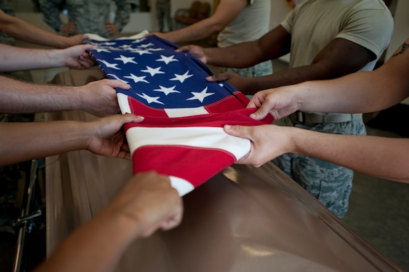 An American flag is folded by the 22nd Air Refueling Wing Honor Guard June 11, 2013, at McConnell Air Force Base, Kan. The folding and presenting of the flag is part of every full-honors veteran burial service they perform. (U.S. Air Force photo/Airman 1st Class Victor J. Caputo)