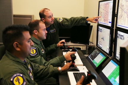 Front to back: Staff Sgt. Jesus, 558th Flying Training Squadron sensor operator instructor, and 2nd Lt. James, 558th FTS Remotely Piloted Aircraft pilot trainee, are instructed by Capt. Gary, 558th FTS instructor pilot on weapons employment procedures. (U.S. Air Force photo by Airman 1st Class Alexandria Slade/Photo illustration by Maggie Armstrong)