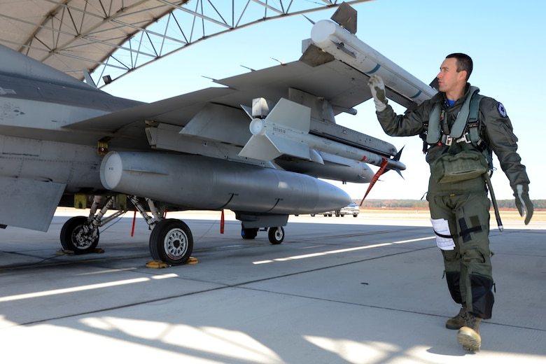 """U.S. Air Force Lt. Col. Michael Ferrario, an F-16 fighter pilot with the South Carolina Air National Guard, performs a pre-flight check on the aircraft in preparation for a flight for the joint Army and Air National Guard training exercise called Carolina Thunder. South Carolina National Guard, along with North Carolina and Georgia National Guard units conducted """"Carolina Thunder 14"""",  a drill weekend, joint training exercise Nov. 15, 2014. More than 30 aircraft participated in the mass take-off from McEntire Joint National Guard Base, Eastover, S.C. Units conducted air and ground operations at the Savannah River Site in Allendale, S.C. The S.C. Air National Guard 169th Fighter Wing's F-16 Fighting Falcons joined AH-64D Apaches, CH-47 Chinooks, UH-60 Black Hawks and more than 100 Infantry Soldiers from the S.C. Army National Guard to train with Apaches from the N.C. Army National Guard and the Joint Surveillance Target Attack Radar System (JSATRS) and Joint Terminal Training Center (JTAC) from the Georgia Air National Guard in a collective force-on-force, enemy suppression and assault mission. (U.S. Air National Guard photo by Amn Megan Floyd/Released)"""