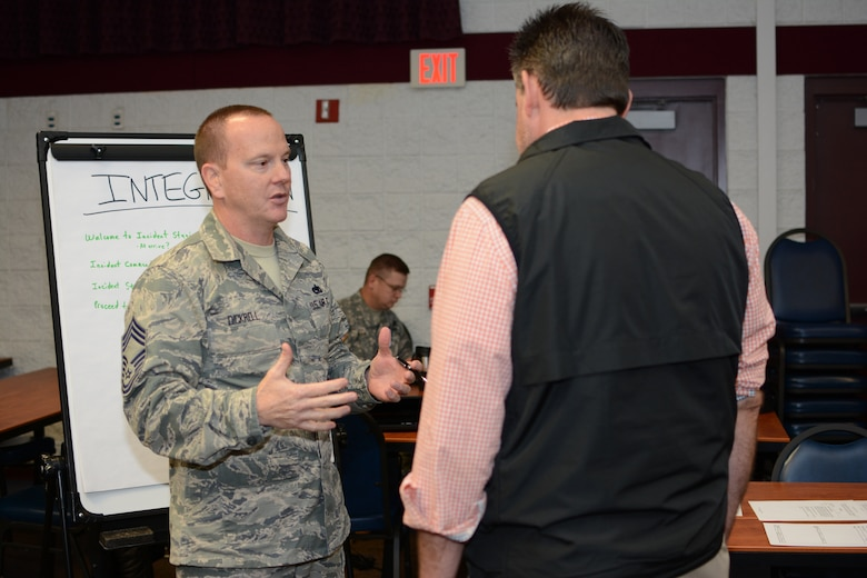 Chief Master Sgt. Alan Dickrell, 115th Fighter Wing force support squadron superintendent, discusses his integration station during the unified reception, staging, onward movement and integration exercise at Volk Field Air National Guard Base, Camp Douglas, Wis., Nov. 19, 2014. The URSOI training and exercise event lasted three days and tested the knowledge and response capabilities of Wisconsin's civilian and military personnel during emergency situations. (U.S. Air National Guard photo by Senior Airman Andrea F. Rhode)