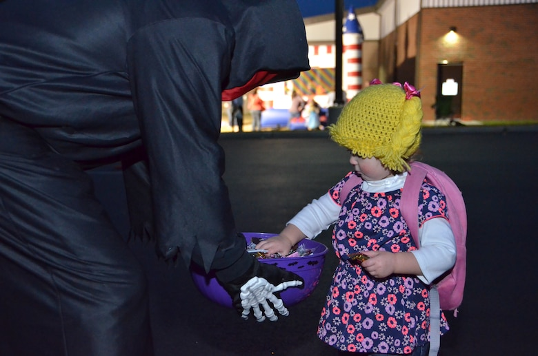 Lylah Chadbourne, 1, daughter of Tech. Sgt. Morgan Chadbourne, a resource advisor for the 103rd Maintenance Group, grabs a handful of candy form a spooky robed skeleton during the first-ever Trunk or Treat event held at Bradley Air National Guard Base, East Granby, Conn., Oct. 28, 2014.  The event was arranged by the Connecticut National Guard's Child and Youth Program and staffed by volunteers who dressed up their car trunks with Halloween decorations. (U.S. Air National Guard photo by Tech. Sgt. Joshua Mead)