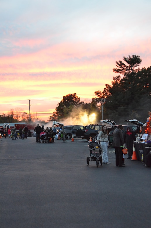 The sun sets as members of the Connecticut National Guard participate in the first annual Trunk or Treat at Bradley Air National Guard Base, East Granby, Conn., Oct. 28, 2014. Walking from car to car, participants are able to trick or treat for candy in a safe environment and enjoy the festive atmosphere offered by the decorated vehicles. (U.S. Air National Guard photo by Tech. Sgt. Joshua Mead)