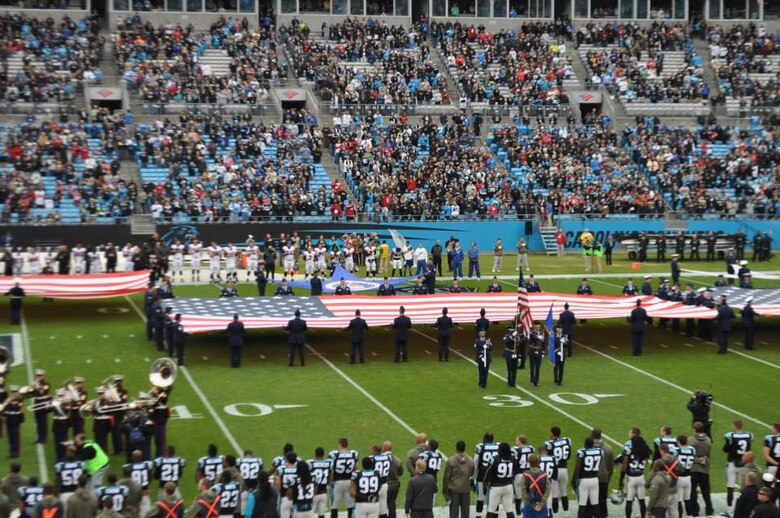 U.S. Air Force Airmen hold a United States flag during the presentation of the colors at the Carolina Panthers Salute to Service game at Bank of America Stadium, Charlotte, N.C., Nov. 16, 2014. The colors were presented by service members from all five branches of the military. (Courtesy photo)