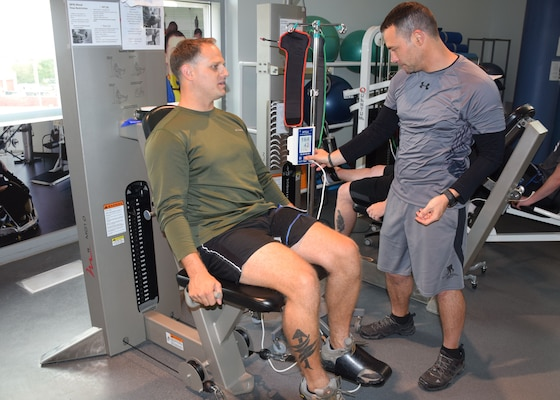 Johnny Owens, chief of the Human Performance Optimization Program, adjusts a setting on a tourniquet worn by Marine Corps Staff Sgt. Brandon Kothman during blood flow restriction training at the Center for the Intrepid's outpatient rehabilitation center, Brooke Army Medical Center, Texas. Owens implemented the groundbreaking program to help wounded service members build muscle strength and function. U.S. Army photo by Robert D'Angelo