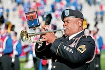 Sgt. 1st Class Frank McCaskill, 1st Infantry Division Band, plays taps before the start of the Nov. 8 University of Kansas versus Iowa State University game in Lawrence, Kan. KU paid tribute to veterans during the Salute to Service game, which included appearances by the 1st Inf. Div. Band; Commanding General's Mounted Color Guard; Fort Leavenworth, Kan., officials; KU ROTC cadets; and a World War II veteran.