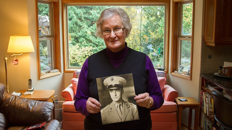 """Barbara Kenney displays a photo of her late father, U.S. Marine 1st Lt. George Greeley Wells, at her home in Bellevue, Washington, Oct. 25, 2014. Greeley served as the adjutant of 2nd Battalion, 28th Marine Regiment, 5th Marine Division, during World War II's famed Battle of Iwo Jima. He carried the first flag that was raised on Mt. Suribachi, a moment later captured by Associated Press photographer Joe Rosenthal in the war's most famous photo. In the 1990s and early 2000s, he was featured in James Bradley's best-selling book """"Flags of Our Fathers"""" and """"War Stories with Oliver North,"""" produced by the retired Marine and Fox News correspondent. Greeley, a native of Lake Forest, Illinois, moved with his family from Harding Township, New Jersey, to Bellevue in the early 2000s. At 94, he passed away in his sleep here Sept. 22, 2014."""