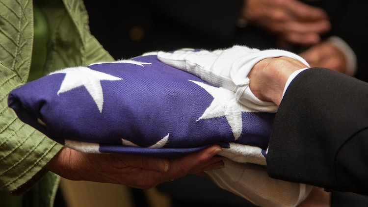 """Maj. Stephen Harding, a supply officer with Combat Logistics Battalion 23, presents a flag on behalf of 35th Commandant of the Marine Corps Gen. James Amos to Barbara Kenney during a memorial service for her father, 1st Lt. George Greeley Wells, in Bellevue, Washington, Oct. 25, 2014. Greeley served as the adjutant of 2nd Battalion, 28th Marine Regiment, 5th Marine Division, during World War II's famed Battle of Iwo Jima. He carried the first flag that was raised on Mt. Suribachi, a moment later captured by Associated Press photographer Joe Rosenthal in the war's most famous photo. In the 1990s and early 2000s, he was featured in James Bradley's best-selling book """"Flags of Our Fathers"""" and """"War Stories with Oliver North,"""" produced by the retired Marine and Fox News correspondent. Greeley, a native of Lake Forest, Illinois, moved with his family from Harding Township, New Jersey, to Bellevue in the early 2000s. At 94, he passed away in his sleep here Sept. 22, 2014."""