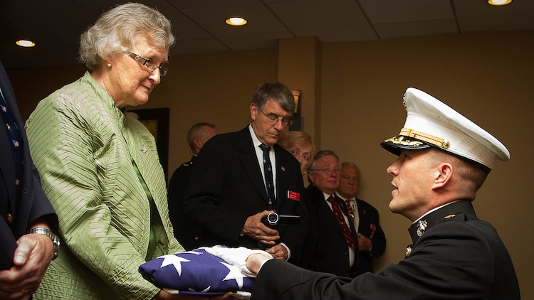 """Maj. Stephen Harding, a supply officer with Combat Logistics Battalion 23, presents a flag on behalf of 35th Commandant of the Marine Corps Gen. James Amos to Barbara Kenney during a memorial service for her father, 1st Lt. George Greeley Wells, in Bellevue, Wash., Oct. 25, 2014. Greeley served as the adjutant of 2nd Battalion, 28th Marine Regiment, 5th Marine Division, during World War II's famed Battle of Iwo Jima. He carried the first flag that was raised on Mt. Suribachi, a moment later captured by Associated Press photographer Joe Rosenthal in the war's most famous photo. In the 1990s and early 2000s, he was featuring in James Bradley's best-selling book """"Flags of Our Fathers"""" and """"War Stories with Oliver North,"""" produced by the retired Marine and Fox News correspondent. Greeley, a native of Lake Forest, Ill., moved with his family from Harding Township, N.J., to Bellevue in the early 2000s. At 94, he passed away in his sleep here Sept. 22, 2014."""