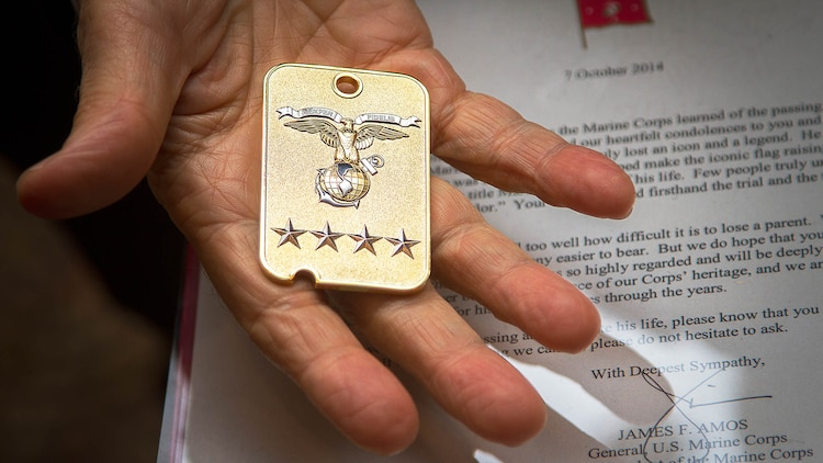 """Greeley Wells Jr., the son of U.S. Marine veteran 1st Lt. George Greeley Wells, displays a challenge coin and letter he received on behalf of 35th Commandant of the Marine Corps Gen. James Amos following a memorial service for his father in Bellevue, Washington, Oct. 25, 2014. Greeley served as the adjutant of 2nd Battalion, 28th Marine Regiment, 5th Marine Division, during World War II's famed Battle of Iwo Jima. He carried the first flag that was raised on Mt. Suribachi, a moment later captured by Associated Press photographer Joe Rosenthal in the war's most famous photo. In the 1990s and early 2000s, he was featured in James Bradley's best-selling book """"Flags of Our Fathers"""" and """"War Stories with Oliver North,"""" produced by the retired Marine and Fox News correspondent. Greeley, a native of Lake Forest, Illinois, moved with his family from Harding Township, New Jersey, to Bellevue in the early 2000s. At 94, he passed away in his sleep here Sept. 22, 2014."""