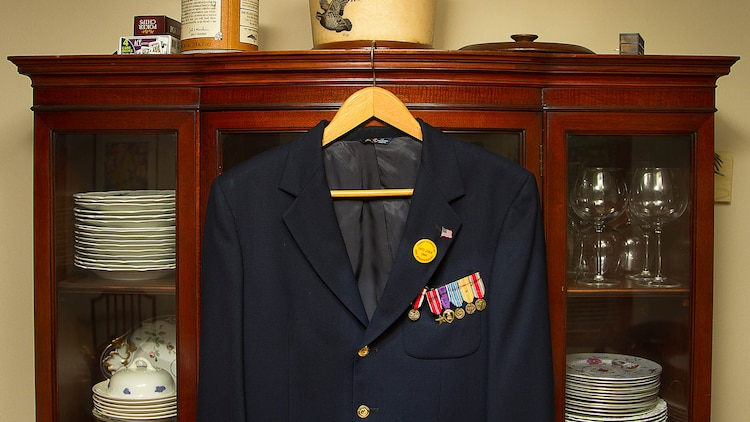 """A suit jacket adorned with military awards earned by U.S. Marine 1st Lt. George Greeley Wells hangs in the home of his daughter Barbara Kenney in Bellevue, Washington, Oct. 25, 2014. Greeley served as the adjutant of 2nd Battalion, 28th Marine Regiment, 5th Marine Division, during World War II's famed Battle of Iwo Jima. He carried the first flag that was raised on Mt. Suribachi, a moment later captured by Associated Press photographer Joe Rosenthal in the war's most famous photo. In the 1990s and early 2000s, he was featured in James Bradley's best-selling book """"Flags of Our Fathers"""" and """"War Stories with Oliver North,"""" produced by the retired Marine and Fox News correspondent. Greeley, a native of Lake Forest, Illinois, moved with his family from Harding Township, New Jersey, to Bellevue in the early 2000s. At 94, he passed away in his sleep here Sept. 22, 2014."""