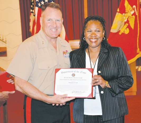 Maj. Gen. John J. Broadmeadow, commanding general, Marine Corps Logistics Command, presents Michelle Polk, with a certificate during a ceremony at Marine Corps Logistics Base Albany's Chapel of the Good Shepherd, recently. Polk, deputy director, Command, Control, Communications and Computers, LOGCOM, retired after more than three decades of civil service to country, Corps.