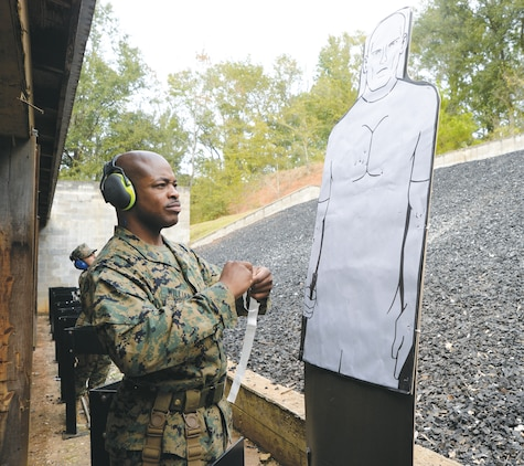 Sgt. Lester Williams, mechanic, Motor Transport,  Marine Corps Logistics Command, pastes shot holes during Combat Pistol Program qualifications, recently, at Marine Corps Logistics Base Albany's pistol range.