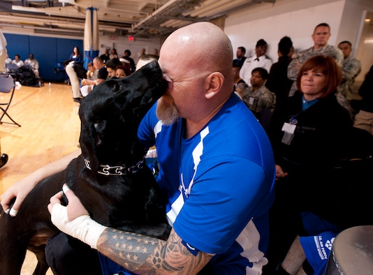 Retired Tech. Sgt. Keith Sekora receives a kiss from his dog, Pintler, during the 4th Annual Pentagon Sitting Volleyball Tournament Nov. 20, 2014, at the Pentagon Athletic Club.  In conjunction with Warrior Care Month, wounded warriors from each service's warrior transition units, as well as U.S. Special Operations Command, participated in the tournament. Sekora received a Silver Medal for Compound Team Archery in the Warrior Games 2013. (U.S. Air Force photo/Staff Sgt. Anthony Nelson Jr.)
