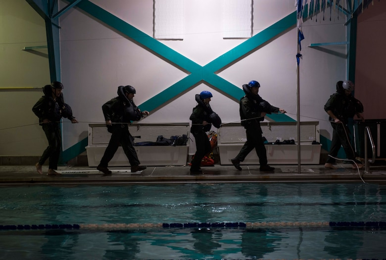 Aircrew members participating in a water and combat survival training course walk with a pulley system used to replicate the sensation of being dragged through water Nov. 4, 2014, at the Minot Air Force Base, N.D., base pool. The course teaches survival techniques for aviators in the event their aircraft were to ever crash land or be shot down over water. (U.S. Air Force photo/Airman 1st Class Lauren Pitts)