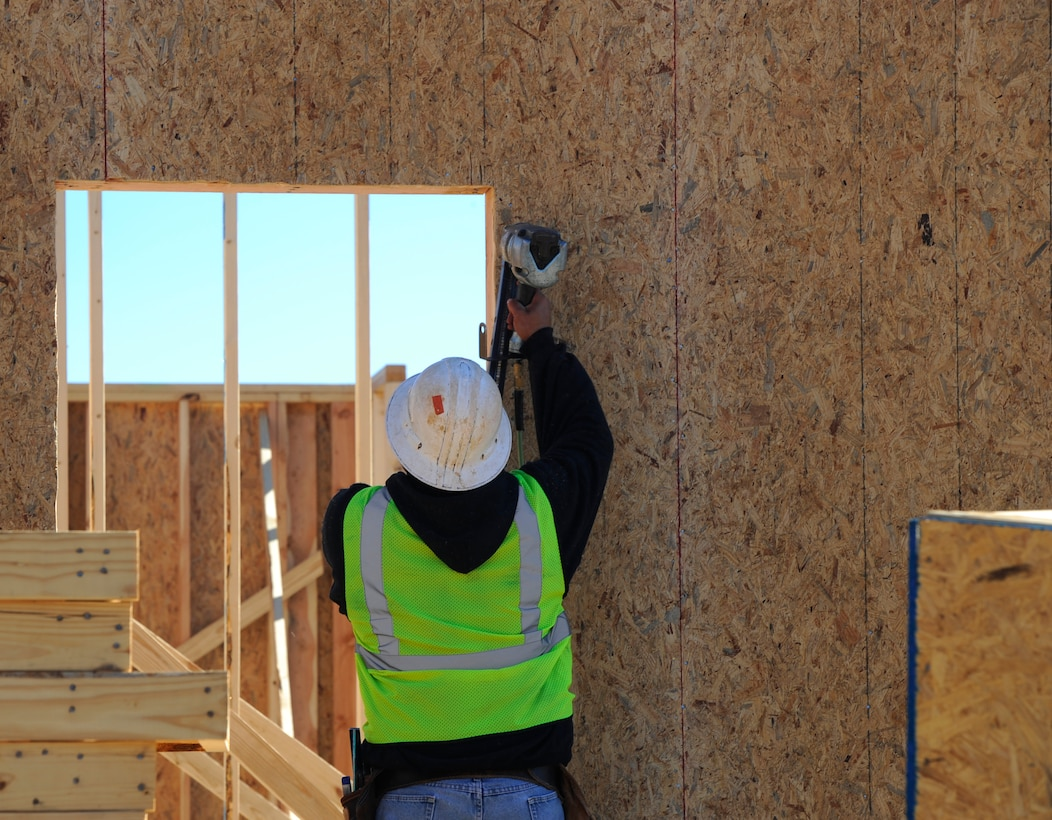 A construction worker secures a wall of a house at the Osprey Landing Neighborhood construction site on Hurlburt Field, Fla., Nov. 18, 2014. Once the homes are completed, they will be turned over to Corvias property management to be assigned to Hurlburt members and their families. (U.S. Air Force photo/Staff Sgt. Sarah Hanson)