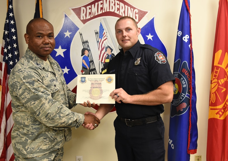Brandon Elson, Buckley Fire Emergency Services, receives an Air Force Space Command Fire Emergency Services Save Certificate from Col. George Petty, AFSPC Civil Engineer Readiness and Emergency Management chief, Nov. 20, 2014, at the fire department on Buckley Air Force Base, Colo. Elson and three other firefighters were awarded for their lifesaving actions while responding to a major vehicle accident in October 2014. (U.S. Air Force photo by Tech. Sgt. Kali L. Gradishar/Released)