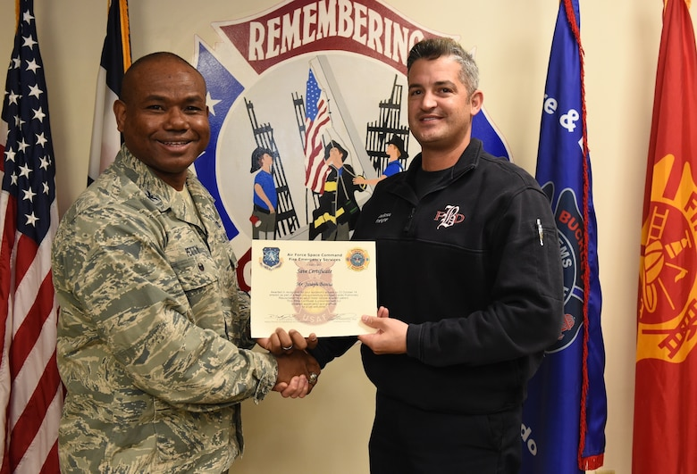 Joseph Boscia, Buckley Fire Emergency Services, receives an Air Force Space Command Fire Emergency Services Save Certificate from Col. George Petty, AFSPC Civil Engineer Readiness and Emergency Management chief, Nov. 20, 2014, at the fire department on Buckley Air Force Base, Colo. Boscia and three other firefighters were awarded for their lifesaving actions while responding to a major vehicle accident in October 2014. (U.S. Air Force photo by Tech. Sgt. Kali L. Gradishar/Released)