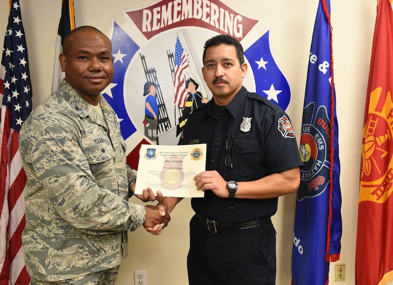 Carlos Hidalgo, Buckley Fire Emergency Services, receives an Air Force Space Command Fire Emergency Services Save Certificate from Col. George Petty, AFSPC Civil Engineer Readiness and Emergency Management chief, Nov. 20, 2014, at the fire department on Buckley Air Force Base, Colo. Hidalgo and three other firefighters were awarded for their lifesaving actions while responding to a major vehicle accident in October 2014. (U.S. Air Force photo by Tech. Sgt. Kali L. Gradishar/Released)