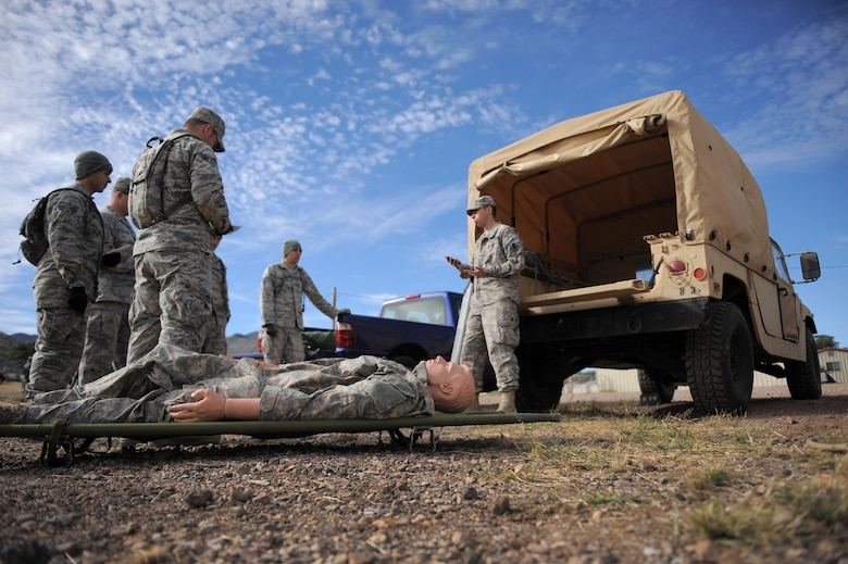 U.S. Army Sgt. Patrick Horton, U.S. Army Intelligence Center of Excellence instructor and course writer, instructs Airmen on how to properly load a casualty into a Humvee during the Army Weather Support Course at Fort Huachuca, Ariz., Nov. 19, 2014. During the course, all participants become certified combat life savers, in case they find themselves in a situation downrange where medics are unavailable. (U.S. Air Force photo by Airman 1st Class Chris Drzazgowski/Released)