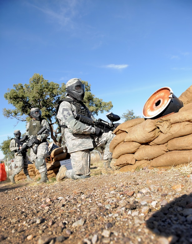 U.S. Air Force Airmen wait for further instruction during a field training exercise at Fort Huachuca, Ariz., Nov. 18, 2014. The Airmen were challenged to defend against simulated opposing forces using paintball guns and Army ground tactics during the Army Weather Support Course. (U.S. Air Force photo by Airman 1st Class Chris Drzazgowski/Released)