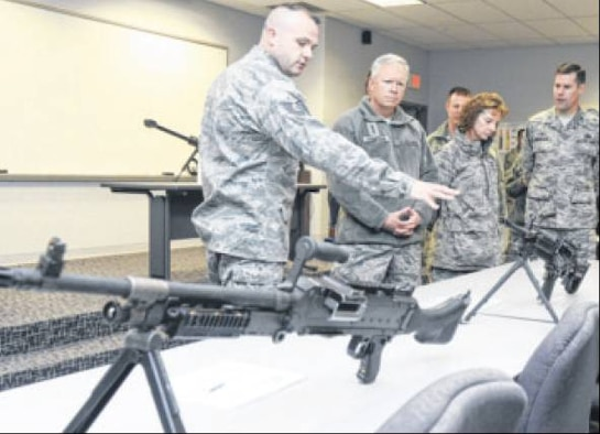 Tech. Sgt Sean Bowes, 88th Security Forces Squadron Combat Army Training and Maintainance (CATM) non-commissioned officer in charge, shows Lt. Gen. John Thompson, Air Force Life Cycle Management Center commander, some of the various weapons the base has access to during Thompson's tour of the 88th Air Base Wing on Nov. 13. Other stops included the Kittyhawk Pharmacy, 88th Operations Support Squadron, 88th Medical Group, the 88th Communications Group and the base recycling center. Looking on during the CATM stop are Chief Master Sgt. Doreen Losacco, AFLCMC commnad chief, Chief Master Sgt. Charles Hoffman, 88th ABW command chief, and Col. John Devillier, 88th ABW commander. (Air Force Photos by Wesley Farnsworth)