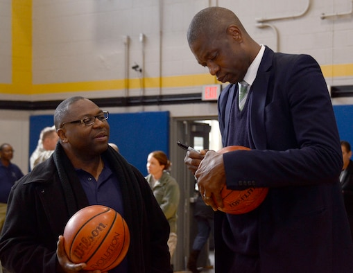 Dikembe Mutombo, NBA Hall of Famer, signs a basketball for a member of Team Dobbins at the grand opening of the renovated fitness center at Dobbins Air Reserve Base, Ga. Nov. 18, 2014. The fitness center includes approximately 30 new pieces of equipment. (U.S. Air Force photo by Don Peek/Released)