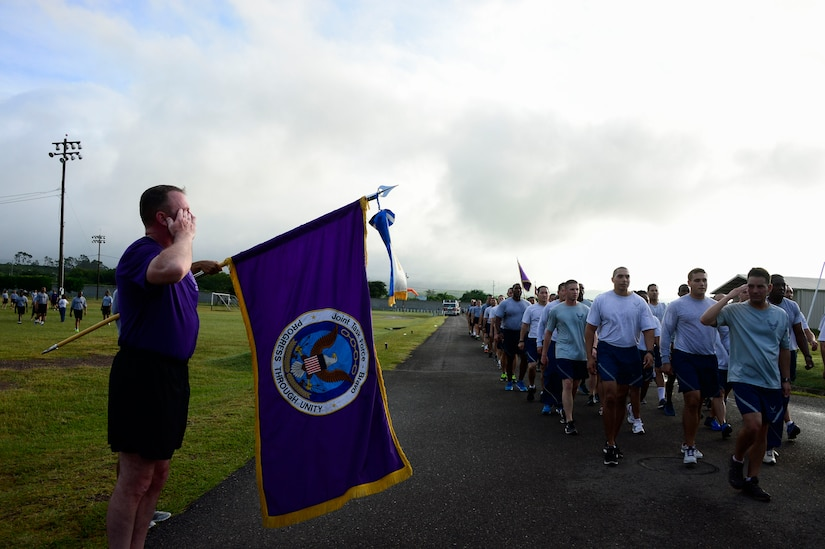 U.S. Army Col. Kirk Dorr, Joint Task Force-Bravo commander, salutes each of the major subordinate commands as they finish the quarterly JTF-Bravo four-mile run at Soto Cano Air Base, Honduras, Nov. 21, 2014.  Once a quarter JTF-Bravo holds a formation run to encourage esprit de corps and physical fitness. (U.S. Air Force photo/Tech. Sgt. Heather Redman)
