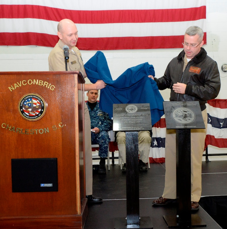 Cmdr. Patrick Boyce, Naval Consolidated Brig Charleston commanding officer (right), and Cmdr. Joseph Cole, NCBC executive officer, unveil two plaques Nov. 21, 2014, in honor of the anniversary of the Brig's commissioning 25 years ago. To date, 8,234 prisoners have been incarcerated at the NCBC, receiving rehabilitative treatment in order to return to honorable service as possible or, barring that, returnto civilian life as productive citizens. The Brig has more than 200 staffers, consisting of Navy, Air Force, Marine Corps and Army active-duty military and civilians. (U.S. Air Force photo/Eric Sesit)