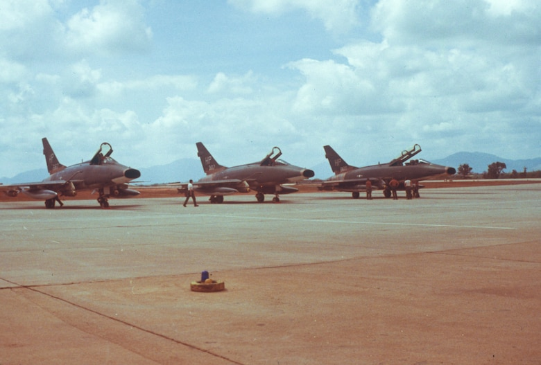 Three U.S. Air Force F-100 Super Sabres from the 355th Tactical Fighter Squadron are looked by maintenance personnel before taking off for combat missions at Phu Cat Air Base, South Vietnam. (Courtesy photo by retired Chief Master Sgt. Richard Newell)