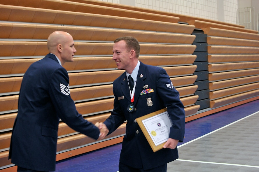 MCGHEE TYSON AIR NATIONAL GUARD BASE, Tenn. - Senior Airman Joseph C. Fiedler III, right, shakes hands with his Airman Leadership School instructor Tech. Sgt. John McClean after receiving his diploma at the I.G. Brown Training and Education Center here Nov. 20 during his class graduation ceremony. At least 273 Airmen and three Coast Guardsmen made up the Paul H. Lankford Enlisted Professional Military Education Center's graduated NCO Academy Class 15-1 and Airman Leadership School Class 15-1. (U.S. Air National Guard photo by Master Sgt. Mike R. Smith/Released)