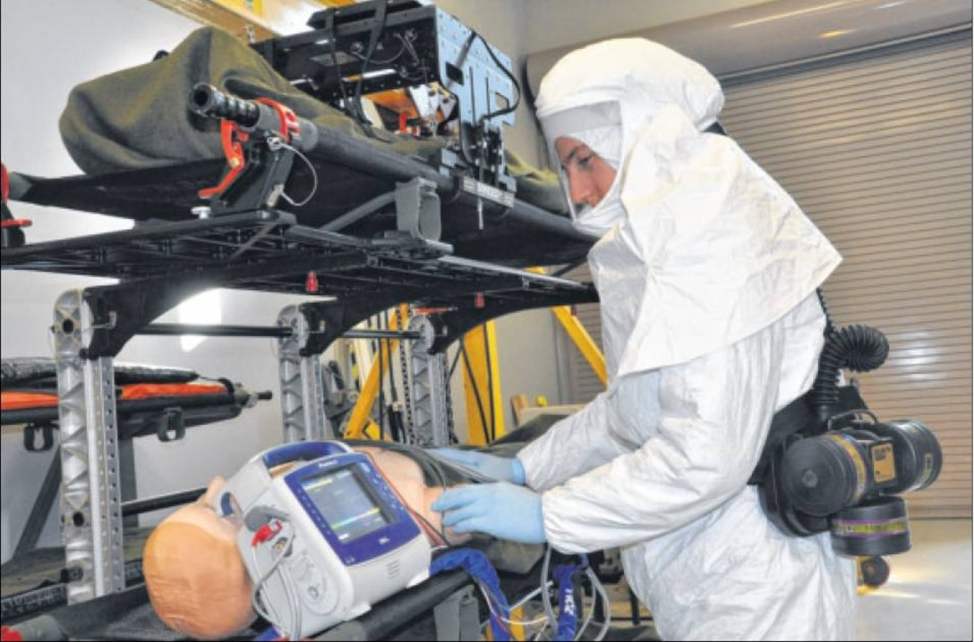 """During a simulation, 2nd Lt. Ray Grothman monitors leads on an """"Ebola patient"""" while wearing the Breathe Easy Powered Air Purifying Respirator around his waist. The respirator would help keep Grothman, or a medical technician, safe while treating the """"patient"""" and is an example of equipment undergoing tests and evaluation by Air Force Life Cycle Management Center personnel in connection with the transport isolation system. (U.S. Air Force photo/John Scaggs)"""