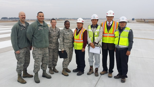 Chong Song-Ho, Kunsan resident office quality assurance representative (4th from right) and Kim U-Kon, Kunsan resident office project engineer (2nd from right) are joined by Airmen from the 8th Civil Engineer Squadron and representatives from Yi Bon Construction Company LTD.