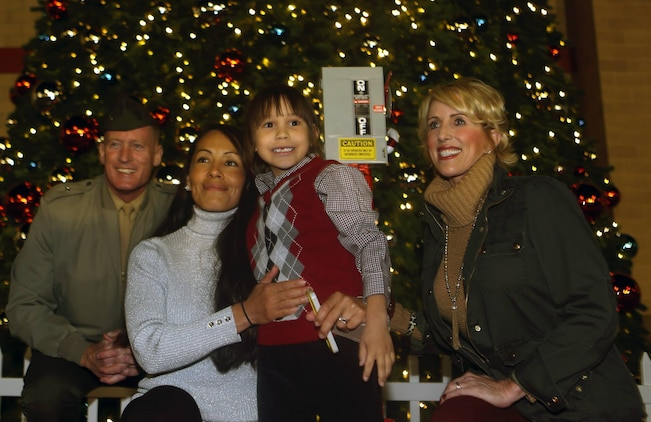 Brig. Gen. Edward D. Banta (left), commanding general of Marine Corps Installations West – Marine Corps Base Camp Pendleton and his wife (right) attend the annual christmas tree lighting ceremony with First Sgt. Christina Hunts Horse-May and her six-year old son, Joseph, at the main exchange, Nov. 22. May's husband signed their son up to flip the switch while on his current deployment with the 5th Marine Regiment.