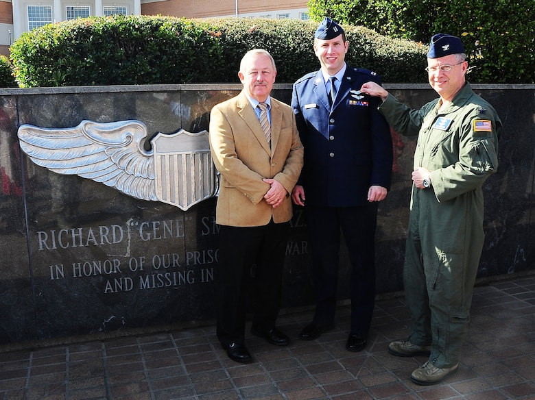 Col. Bill Mueller, Director of the USAF Pilot-Physician Program, Wright-Patterson Air Force Base, Ohio, pins the silver wings of an Air Force pilot to the chest of Capt. William Smith, 14th Flying Training Wing Specialized Undergraduate Pilot Training Class 15-02 student and a prior flight surgeon, with the assistance of Smith's father, Mike, a U.S. Air Force retired master sergeant, at the Gene Smith Memorial Plaza Nov. 21 on Columbus Air Force Base, Miss. Mueller visited the base to congratulate and welcome Smith into the Pilot-Physician program, an elite career field combining two very specialized jobs. (U.S. Air Force photo/Airman John Day)
