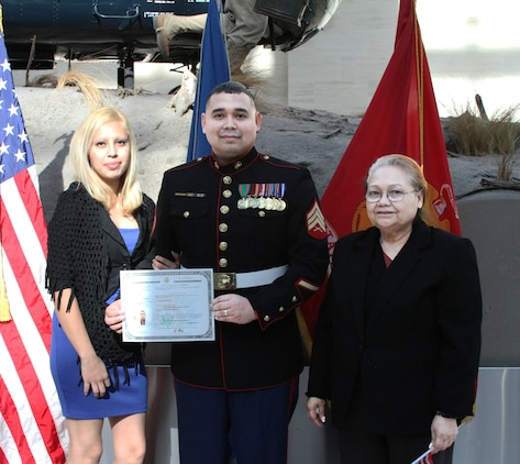 U.S. Marine Corps Sgt. Gustavo A. Arroliga, a recruiter with Recruiting Sub-Station Woodbridge and native of Nicaragua, holds his Certificate of Naturalization of citizenship Nov.  10, 2014. His wife Laura (left) and mother Mercedes Lopez (right) attended this prestigious ceremony at the National Museum of the Marine Corps.  (U.S. Marine Corps photo by Cpl. Amber Williams/Released)