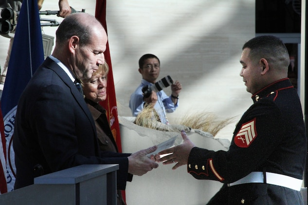 U.S. Marine Corps Sgt. Gustavo A. Arroliga, a recruiter with Recruiting Sub-Station Woodbridge and native of Nicaragua, is presented his certificate of naturalization during a naturalization ceremony held at the national Museum of the Marine Corps Nov. 10, 2014. The director of the U.S. Citizenship and Immigration Services, Leon Rodriguez, presented the certificates at the ceremony held on the 239th birthday of the Marine Corps. (U.S. Marine Corps photo by Cpl. Amber Williams/ Released)