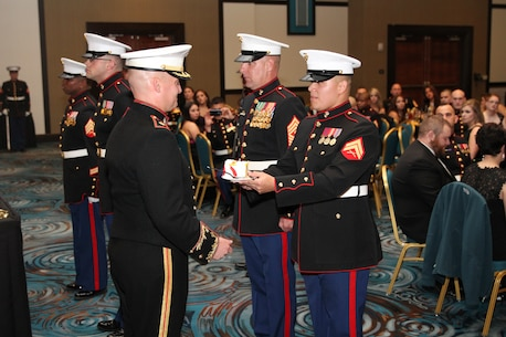 Maj. Andrew Schoenmaker, commanding officer of Marine Corps Recruiting Station Harrisburg, concludes the cake cutting ceremony with Master Gunnery Sgt. James Babst, the oldest Marine present, and Cpl. Manuel Cardenas, the youngest Marine, at the 239th Birthday Ball Celebration at the Mohegan Sun Pocono Downs, Nov. 7, 2014.