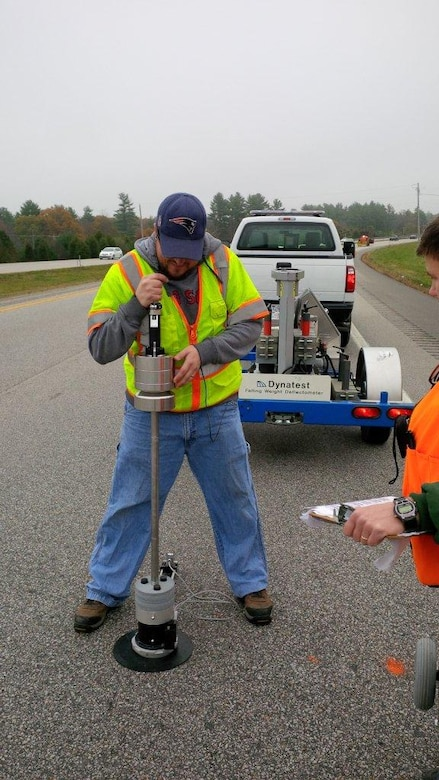CRREL civil engineering technician Andy Bernier uses Light weight deflectometer (LWD) in support of the New Hampshire Department of Transportation (NHDOT) to evaluate a new highway pavement design and construction strategy incorporating geo-grid fabric.  Testing with the falling weight deflectometer (FWD) is shown in the background.