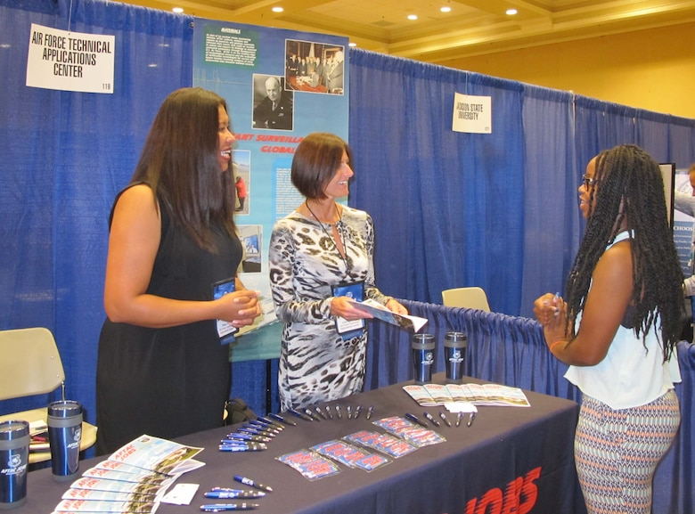 Rose Day, left, and Julia Ignacek, center, answer questions from an attendee of the 41st Annual National Organization for the Professional Advancement of Black Chemists and Chemical Engineers Conference  Sept. 23, 2014, in New Orleans. Day and Ignacek are members of the Air Force Technical Applications Center at Patrick AFB, Fla. The co-workers set up a booth to reach out to a diverse audience of scientists, educators, managers, engineers and students who attended the week-long event. (Courtesy photo)