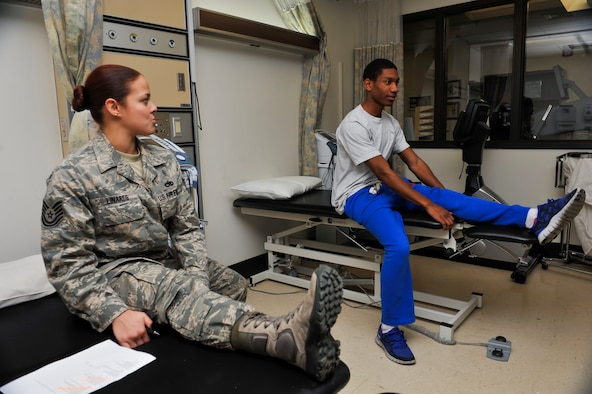 Tech Sgt. Liz Marie Linares, 51st Medical Operations Squadron physical therapy technician, shows Senior Airman Justin Morgan, 25th Aircraft Maintenance Unit weapons loader, how to perform a hamstring stretch during a physical therapy session Nov. 25, 2014, on Osan Air Base, Republic of Korea. The direct access clinic is held to provide treatment for service members who have had an acute musculoskeletal injury within seven-days prior to the visit. (U.S. Air Force photo by Senior Airman David Owsianka)