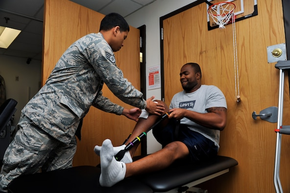 Staff Sgt. Marcos Davis, 51st Medical Operations Squadron physical therapy technician, aids Staff Sgt. Kyle Wimberly, 18th Intelligence Squadron Detachment 2 space systems analyst, with performing an exercise during a physical therapy session Nov. 25, 2014, on Osan Air Base, Republic of Korea. Wimberly is performing the exercise to regain a full range of motion and flexibility in his knee. (U.S. Air Force photo by Senior Airman David Owsianka)
