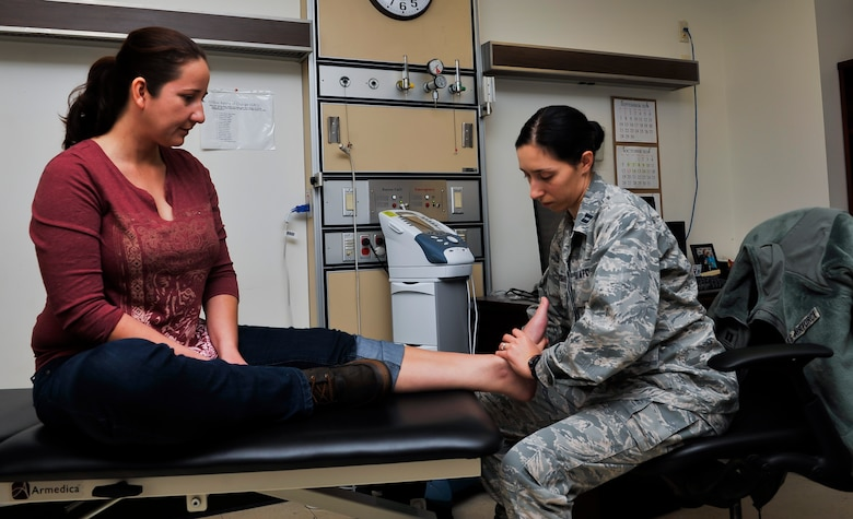 Capt. Veronica Khrakovskaya, 51st Medical Operations Squadron physical therapist, checks the foot of Lori Jonas, spouse of Capt. Jozsef Jonas, 25th Fighter Squadron pilot, during a reassessment session Nov. 25, 2014, on Osan Air Base, Republic of Korea. The direct access clinic is available from 8 a.m. to 10 a.m. on Tuesdays and Thursdays. (U.S. Air Force photo by Senior Airman David Owsianka)
