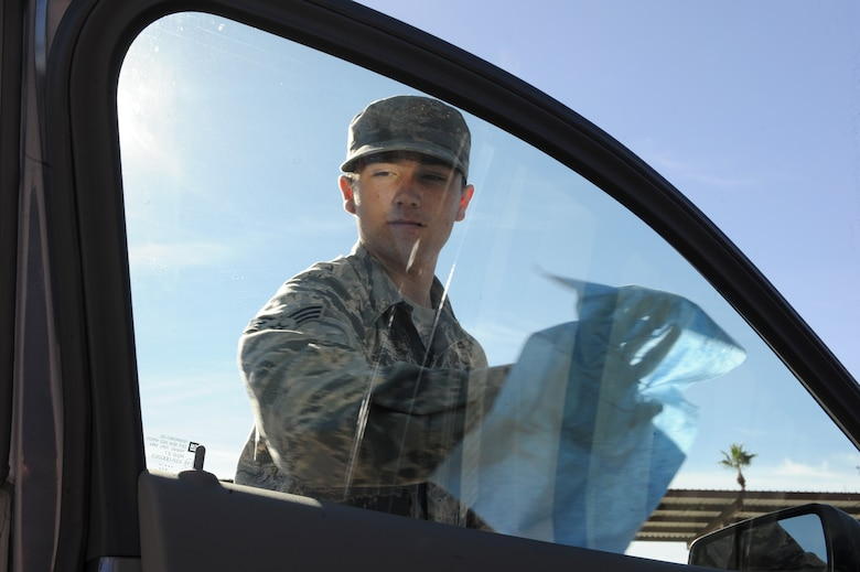 U.S. Air Force Senior Airman Andrew Liszewski, 355th Logistics Readiness Squadron vehicle operator and dispatcher, cleans the window of a government-owned vehicle at Davis-Monthan Air Force Base, Ariz., Nov. 18, 2014. Using a separate cleaner to wash the windows ensures no streaks or water spots remain on the windows for a see through appearance. (U.S. Air Force photo by Airman 1st Class Cheyenne Morigeau/ Released)