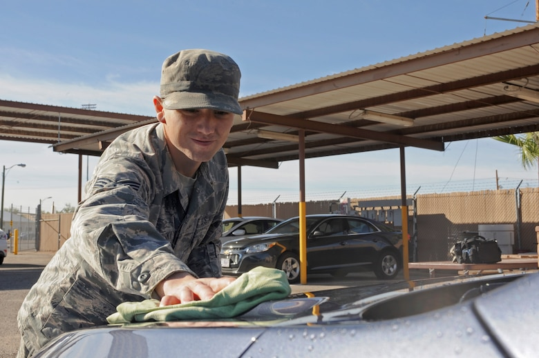U.S. Air Force Senior Airman Andrew Liszewski, 355th Logistics Readiness Squadron vehicle operator and dispatcher, dries a government-owned vehicle at Davis-Monthan Air Force Base, Ariz., Nov. 18, 2014. Drying the vehicle with a towel removes water spots left over from the wash. (U.S. Air Force photo by Airman 1st Class Cheyenne Morigeau/ Released)