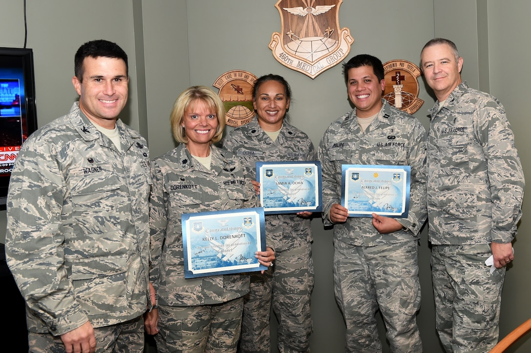 Col. John Wagner, 460th Space Wing commander, left, and Col. Michael Kindt, 460th Medical Group commander, right, surprised three medical group officers with news of their promotion selection Nov. 24, 2014, on Buckley Air Force Base, Colo. The members selected for promotion are, from second from left, Lt. Col. Kelly Dorenkott, 460th Medical Operations Squadron commander, Lt. Col. Samia Ochia, 460th Medical Group staff chief and Capt. Alfred Felipe, 460th Medical Group Bioenvironmental Engineering officer in charge. (U.S. Air Force photo by Airman 1st Class Samantha Saulsbury/Released)
