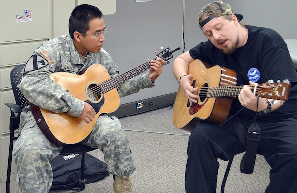 Volunteer instructor Christian Lee (right) works with Spc. Hyson Largo Nov. 12 during a therapeutic music group for Soldiers at Brooke Army Medical Center