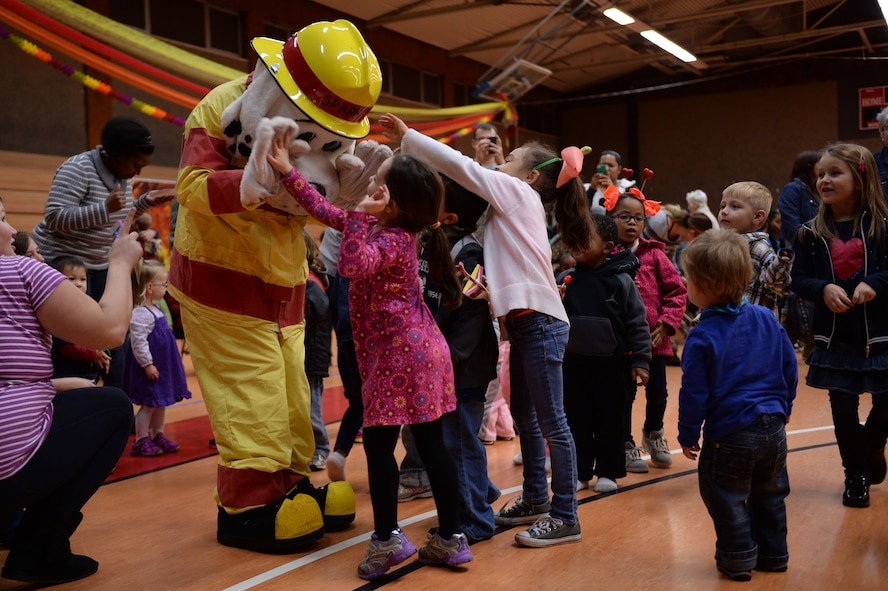 A U.S. Air Force Airman from the 52nd Civil Engineer Squadron fire department dressed as Sparky the Fire Dog high-fives a child during the Spangtacular Family Fall Festival Nov. 21, 2014, in the Skelton Memorial Fitness Center at Spangdahlem Air Base, Germany. Sparky the Fire Dog is the official mascot of the National Fire Protection Agency and made an appearance to interact with the children at the event. (U.S. Air Force photo by Staff Sgt. Daryl Knee/Released)