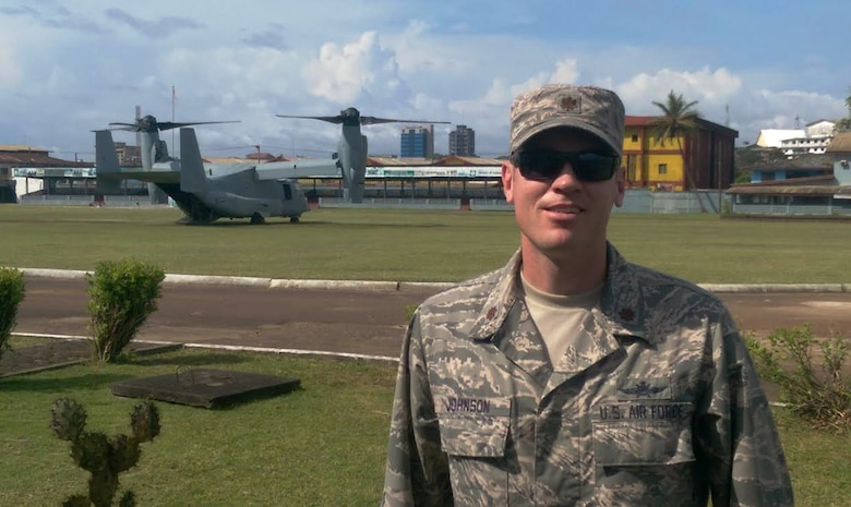 Maj. Kyle Johnson, Africa Command detachment commander, 2nd Joint Communications Squadron, Joint Communications Support Element, pauses for a photo in front of an MV-22 Osprey; the city of Monrovia, Liberia, rises in the background.